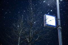 Orologio su un palo della luce Mosca nell'inverno fotografia stock libera da diritti