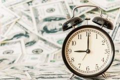 Orologio sul fondo del modello della banconota in dollari di mese dei contanti Fotografie Stock