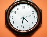 Orologio sulla parete arancione fotografie stock libere da diritti