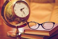 Orologio, vetri e libri sulla tavola fotografie stock