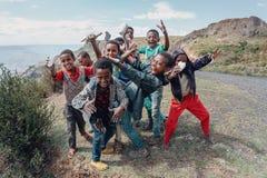 Ethiopian teenager boys posing to tourists. OROMIA REGION, ETHIOPIA, APRIL 19.2019, Group of happy Ethiopian teenager boys on road posing to tourists for photo stock photography
