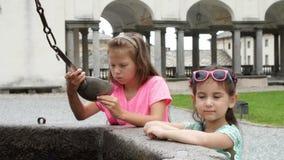OROPA, BIELLA, ITÁLIA - 7 DE JULHO DE 2018: as crianças das meninas bebem a água alpina de prata das cubetas de prata, da máscara filme