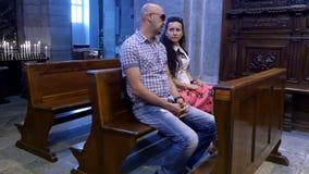 OROPA, BIELLA, ITALIA - 7 DE JULIO DE 2018: la gente, los niños y los adultos están sentando en bancos en una iglesia vieja catól almacen de video