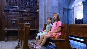 OROPA, BIELLA, ITALY - JULY 7, 2018: children are sitting on a bench in a catholic old church, looking at wall paintings. Shrine of Oropa, Sanctuary, in the stock footage