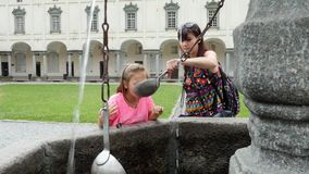 OROPA, BIELLA, ITALY - JULY 7, 2018: tourists drink silver alpine water from silver buckets, from stone gothic mask. Fountain in Shrine of Oropa, Sanctuary, in stock video