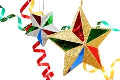 Oropel celebrador multicolor y dos estrellas de la Navidad Fotografía de archivo
