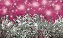 Oropel/guirnalda de plata con el fondo rosado de la chispa Fotos de archivo libres de regalías