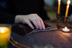 Oroscopi zingareschi degli indovini per i clienti che usando le carte zingaresche premonirici fotografia stock libera da diritti