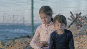 Depressed children. Loneliness girl crying near to sad boy. Sad little refugees Brother and sister on the shore near the state bor stock footage