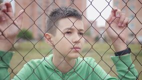 Serious boy stands alone near the fence looks around, holding hands on the wire