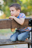 Orphan, unhappy boy sitting on a park bench and crying Stock Images