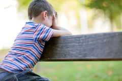 Orphan, unhappy boy sitting on a park bench and crying Royalty Free Stock Photos