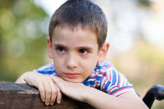 Orphan, unhappy boy sitting on a park bench and crying Stock Photography