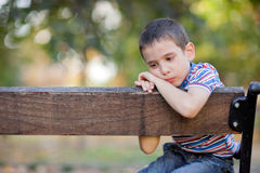 Orphan, unhappy boy sitting on a park bench and crying Royalty Free Stock Image