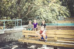 Orphaned children sit in an abandoned park on old benches royalty free stock images