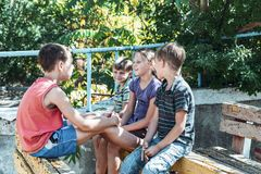 Orphaned children sit in an abandoned park on old benches royalty free stock photography