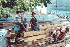 Orphaned children sit in an abandoned park on old benches stock photo