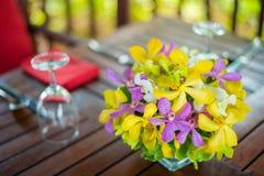 A orquídea colorida no frasco decora na tabela de madeira com a de abastecimento Imagem de Stock