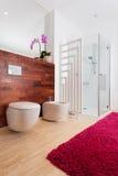 Orquídea y alfombra roja en cuarto de baño Foto de archivo
