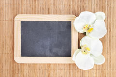 Orquídeas con la pizarra en el fondo de bambú Fotos de archivo libres de regalías