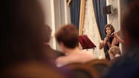 Orquesta de cámara Una mujer joven que toca el violín durante un funcionamiento Gente que mira el funcionamiento almacen de video