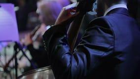 Orquesta sinfónica durante funcionamiento Violinistas y violoncelista que juegan en el concierto, vista posterior almacen de metraje de vídeo