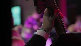 Orquesta sinfónica durante funcionamiento Violinistas y violoncelista que juegan en el concierto, vista posterior almacen de video