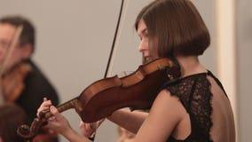 Orquestra de câmara Uma jovem mulher concentrada jogando o violino durante um desempenho Ângulo lateral filme