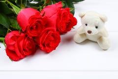 Orsacchiotto bianco circondato dalle rose rosa su una tavola di legno bianca Modello per l'8 marzo, festa della Mamma, San Valent Fotografia Stock Libera da Diritti