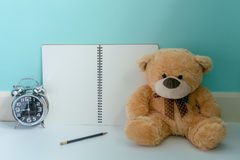 Orsacchiotto che tiene l'orologio brillante con il taccuino della pagina in bianco e Fotografia Stock