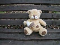 Orsacchiotto d'annata che tiene cuore e che si siede sul banco di legno immagini stock