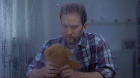 Orsacchiotto di tenuta maschio solo dietro la finestra piovosa, bambino di mancanza dopo il divorzio stock footage