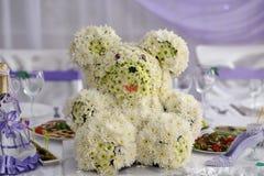 Orsacchiotto fatto dei fiori sulla tavola di nozze fotografie stock