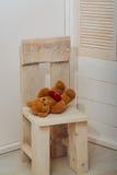 Orsacchiotto marrone sveglio con cuore rosso sulla sedia di legno Immagini Stock Libere da Diritti