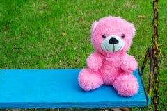 Orsacchiotto rosa lanuginoso che si siede sull'oscillazione d'annata blu Fotografia Stock Libera da Diritti