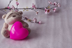 Orsacchiotto sveglio con un cuore su un fondo bianco Fotografie Stock