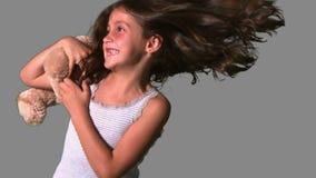 Orsacchiotto volteggiante e di cattura della bambina su fondo grigio video d archivio