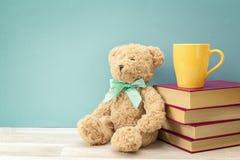 Orso della peluche con la pila di libro e di tazza gialla contro backgr blu Fotografia Stock