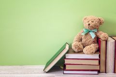 Orso della peluche con la pila di libro su un fondo verde Copi lo spazio Immagini Stock