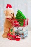 Orso di orsacchiotto di natale che spinge il carrello di acquisto Immagine Stock
