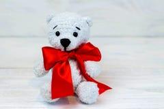 orso tricottato, giocattolo tricottato, amigurumi, su fondo di legno bianco fotografia stock