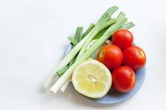 Ortaggi freschi (cipolle, pomodoro e limone) su un piatto blu Fotografia Stock