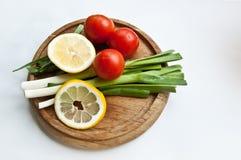Ortaggi freschi (cipolle, pomodoro e limone) su un tagliere Fotografie Stock
