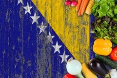 Ortaggi freschi dalla Bosnia-Erzegovina sulla tavola Cottura del concetto sul fondo di legno della bandiera immagine stock