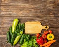 Ortaggi freschi del fondo di legno del tagliere differente di colori Vegetarianismo e nutrizione sana Disposizione piana fotografie stock