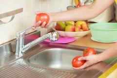 Ortaggi freschi di lavaggio della donna in cucina fotografie stock