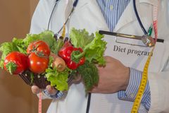 Ortaggi freschi e frutta maschii della tenuta del dietista: concetto vegetariano sano di dieta Ritratto del dietista maschio With fotografia stock libera da diritti