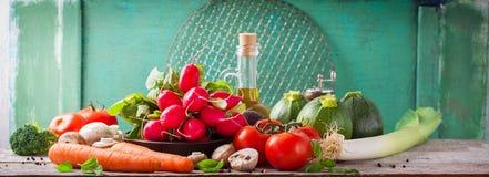 Ortaggi freschi e olio d'oliva su un concetto sano o vegetariano di legno del fondo, fotografia stock