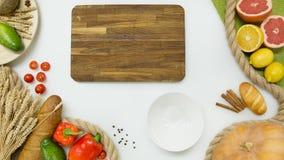 Ortaggi freschi, frutta, tagliere di legno su fondo bianco Fotografia Stock Libera da Diritti