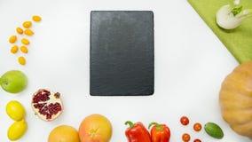 Ortaggi freschi, frutta, tagliere nero su fondo bianco, vista superiore Immagini Stock